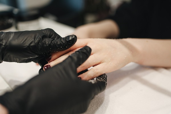 Canva - Person Wearing Black Gloves Massaging a Person's Hand